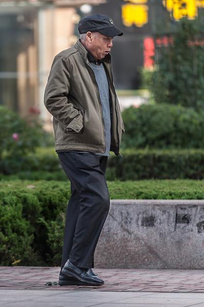 A man strolls along an Anyang sidewalk. (Beiguan Qu, Anyang Shi, Henan Sheng, CN - 10/25/16, 2:57:21 PM)