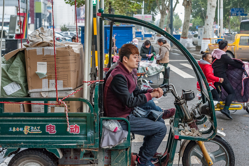 A young man with a fashionable haircut drives his motorised cart throiugh and Anyang intersection. (Beiguan Qu, Anyang Shi, Henan Sheng, CN - 10/23/16, 3:51:30 PM)