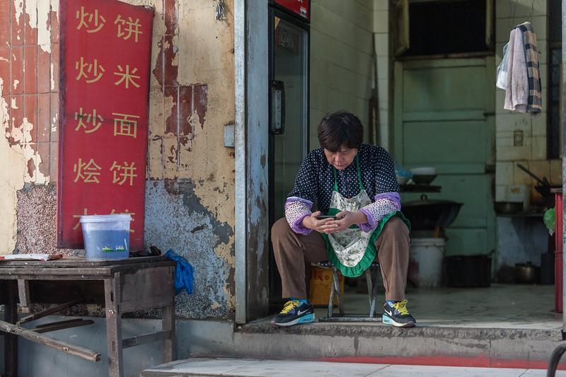 A woman gazes at her smartphone in the entrance to a small Anyang restaurant. (Beiguan Qu, Anyang Shi, Henan Sheng, CN - 10/25/16, 3:11:28 PM)