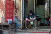 A woman gazes at her smartphone in the entrance to a small Anyang restaurant. (Beiguan Qu, Anyang Shi, Henan Sheng, CN - 10/25/16, 3:11:28 PM)