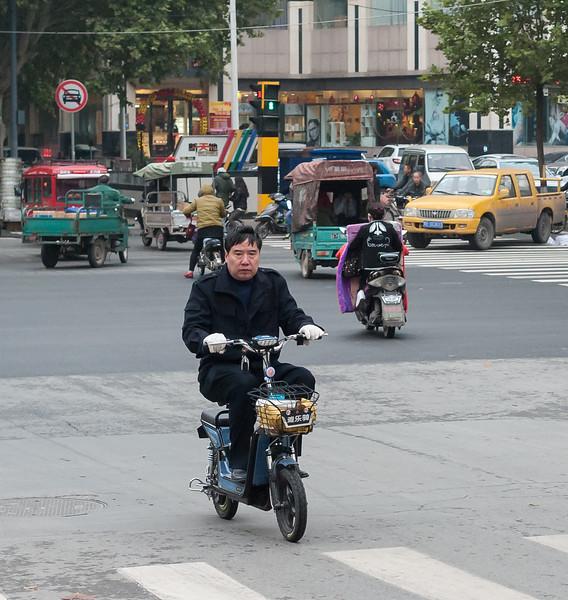 A man rides his scooter through an Anyang intersection. (Beiguan Qu, Anyang Shi, Henan Sheng, CN - 10/23/16, 4:39:30 PM)