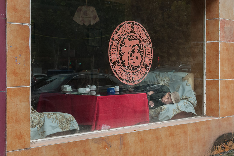 A man takes a nap during the afternoon rest hours on a couch in an Anyang restaurant. (Beiguan Qu, Anyang Shi, Henan Sheng, CN - 10/23/16, 4:34:31 PM)