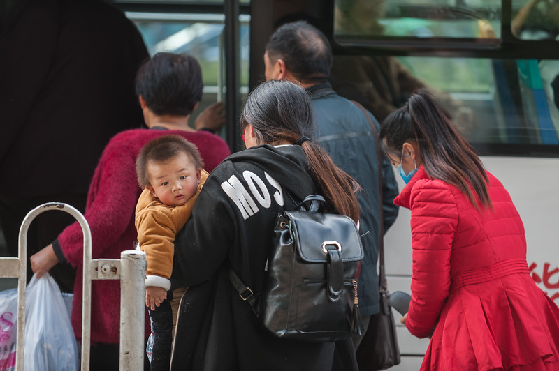 A young boy contempates your intrepid photographer as he and his mom prepare to board an Anyang bus. (Beiguan Qu, Anyang Shi, Henan Sheng, CN - 10/25/16, 2:54:57 PM)