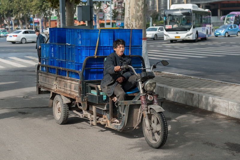 A man yawns while hauling goods on his motorized cart on an Anyang street. (Beiguan Qu, Anyang Shi, Henan Sheng, CN - 10/24/16, 10:25:14 AM)