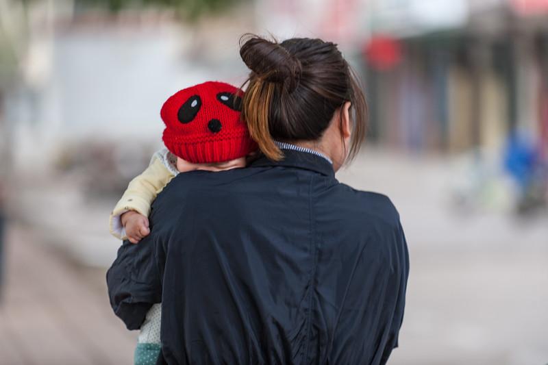 A woman walks with her sleeping baby in central Anyang. (Beiguan Qu, Anyang Shi, Henan Sheng, CN - 10/25/16, 3:04:56 PM)
