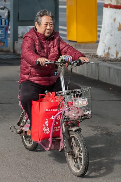 A woman navigates her scooter down an Anyang road. (Beiguan Qu, Anyang Shi, Henan Sheng, CN - 10/24/16, 10:25:29 AM)