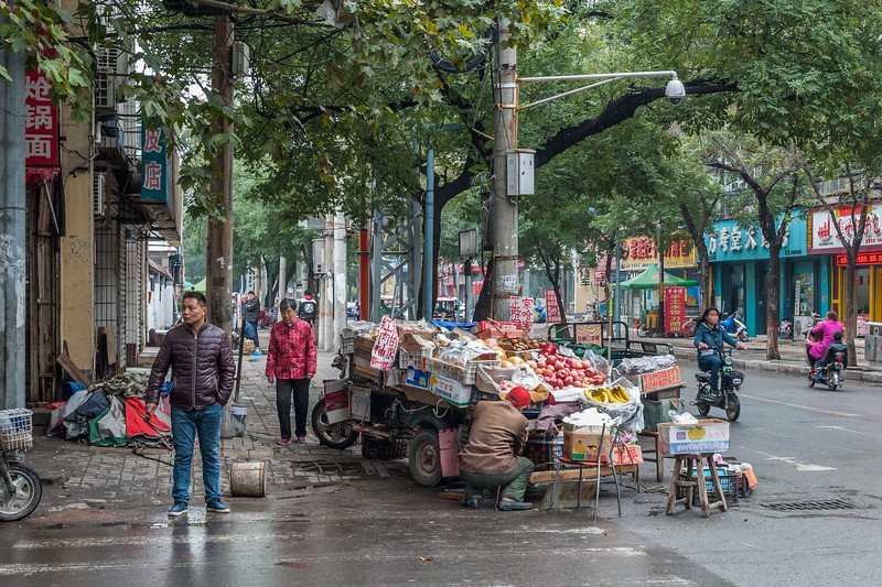 A purveyor of fruit awaits customers on an Anyang sidewalk. (Beiguan Qu, Anyang Shi, Henan Sheng, CN - 10/23/16, 3:45:10 PM)