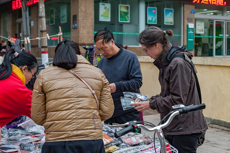 The archaeologist Katrinka Reinhart shops for gloves at a pop-up sidewalk sale in central Anyang. (Beiguan Qu, Anyang Shi, Henan Sheng, CN - 10/23/16, 4:37:10 PM)