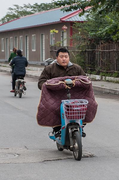 A man rides his scooter on the main street of Xiaotun Village. (Yindu Qu, Anyang Shi, Henan Sheng, CN - 10/24/16, 11:40:45 AM)