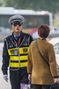 A passerby looks at an Anyang traffic control officer. (Beiguan Qu, Anyang Shi, Henan Sheng, CN - 10/25/16, 2:47:25 PM)
