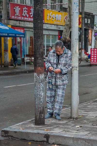 A man sporting his pajamas reclines on a lightpost on an Anyang sidewalk. (Beiguan Qu, Anyang Shi, Henan Sheng, CN - 10/23/16, 3:47:24 PM)