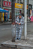 A man sporting his pajamas reclines on a lightpost on an Anyang sidewalk. (Beiguan Qu, Anyang Shi, Henan Sheng, CN - 10/23/16, 3:47:24 PM)