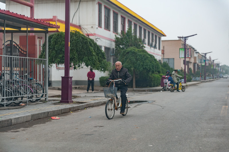 A man rides his bike on the main street of Anyang's Xiaotun Village. (Yindu Qu, Anyang Shi, Henan Sheng, CN - 10/26/16, 4:15:59 PM)