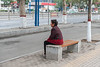 A woman rests on an Anyang sidewalk bench. (Beiguan Qu, Anyang Shi, Henan Sheng, CN - 10/24/16, 2:25:21 PM)