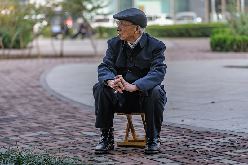An elderly man sits contemplatively on an Anyang sidewalk. (Beiguan Qu, Anyang Shi, Henan Sheng, CN - 10/25/16, 2:58:50 PM)