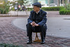 An elderly man sits contemplatively on an Anyang sidewalk. (Beiguan Qu, Anyang Shi, Henan Sheng, CN - 10/25/16, 2:58:50 PM)