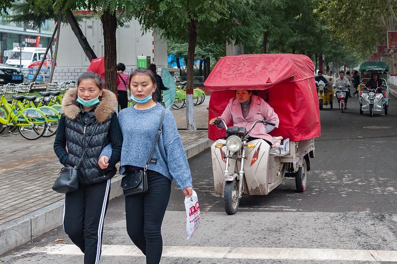 Two young women walk arm-in-arm on an Anyang street. (Beiguan Qu, Anyang Shi, Henan Sheng, CN - 10/23/16, 3:52:23 PM)