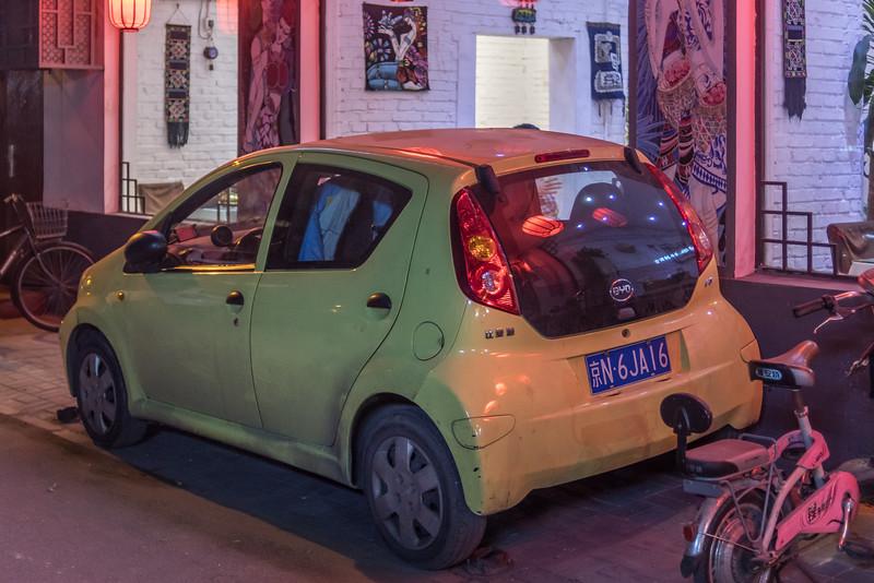 A car is parked next to a restaurant in a Beijing hutong. (Dongcheng Qu, Beijing, CN - 11/01/16, 6:08:02 PM)