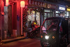 A man drives a three-wheeled vehicle past shops and restaurants in a Beijing hutong. (Dongcheng Qu, Beijing, CN - 11/01/16, 6:08:43 PM)