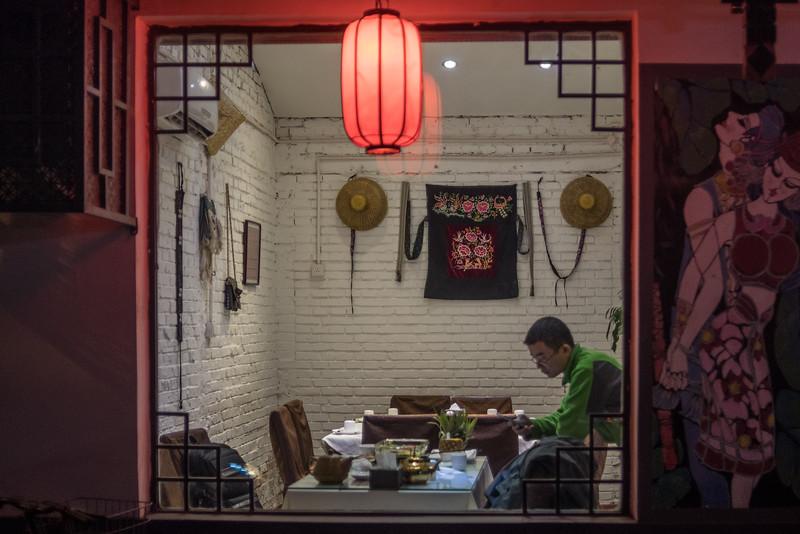 A man looks at his phone inside a hutong retaurant. (Dongcheng Qu, Beijing, CN - 11/01/16, 6:09:03 PM)