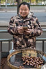 A street vendor smiles while selling roasted chestnuts on a Dongdan Street sidewalk in Beijing. (Dongcheng Qu, Beijing, CN - 11/01/16, 4:48:50 PM)