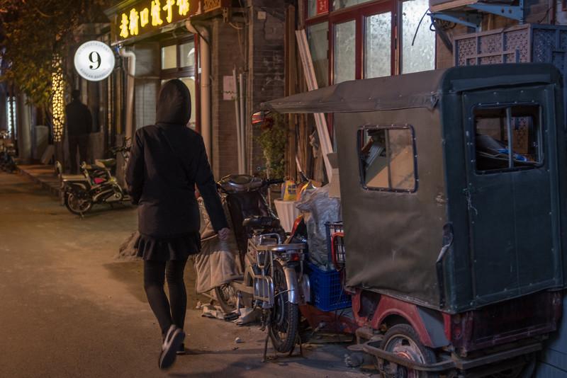 A woman walks toward a restaurant in a Beijing hutong. (Dongcheng Qu, Beijing, CN - 11/01/16, 6:03:01 PM)