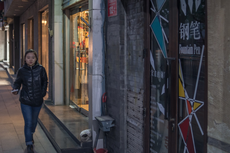A woman walks by shops on a side street in Beijing's Dongcheng district. (Dongcheng Qu, Beijing, CN - 11/01/16, 5:23:56 PM)