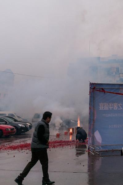 Lighting fireworks on a rainy morning wedding (Yanshi, Henan, CN - 10/31/13, 11:28:21 AM)
