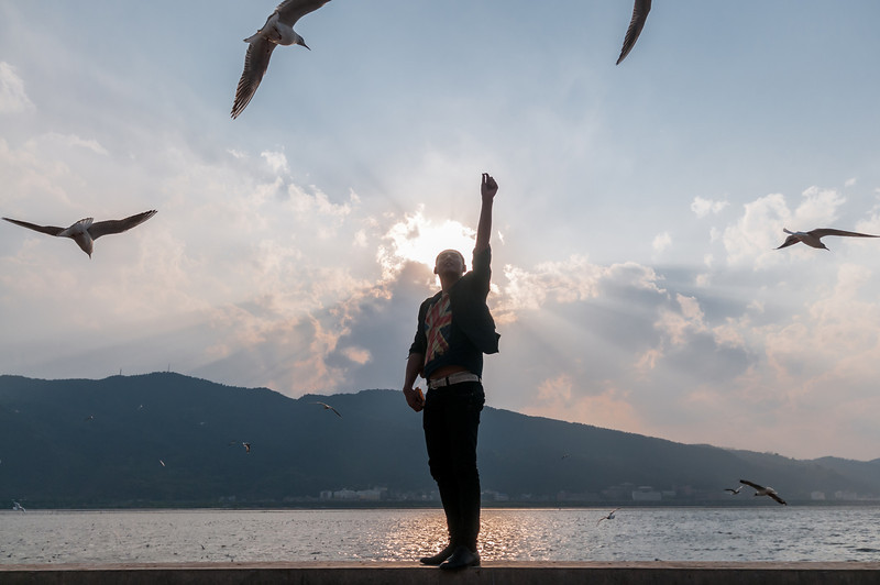 A friend feeds seagulls at Dianchi Lake (Xishan, Kunming, Yunnan, CN - 03/19/13, 5:51:56 PM)