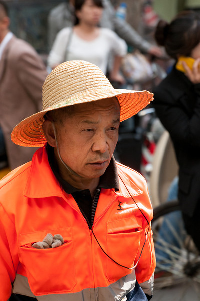 Cityworker in fluorescent uniform stands out in a crowd (Kunming, Yunnan, CN - 03/19/13, 4:23:17 PM)
