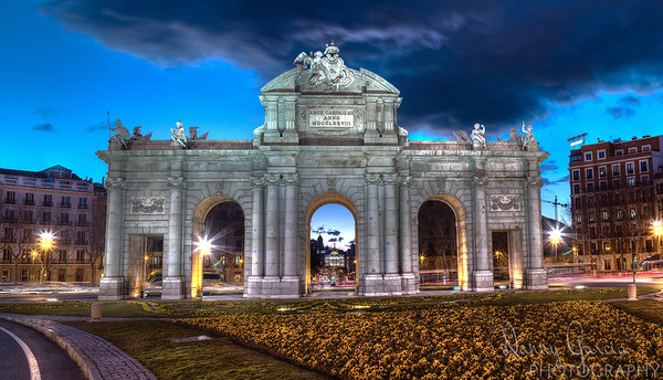 """Puerta de Alcala was inaugurated in 1778... in the distance viewable through the arch is The Metropolis Building which stands from just 1911.  8755 x 5025 pixels!! That translates into a 36 x 20"""" print without even having to enlarge it! That's a 44 MEGAPIXEL image!  This was composed of a total of 15 shots to create 5 slices, then stitched together. For the photo geeks: ISO 100, 28mm, at f/11... shortest exposure .5 sec, longest @ 6 seconds."""