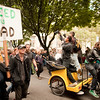 Photographers ride on a bike taxi through the crowd at the Occupy Portland movement in Portland Oregon.