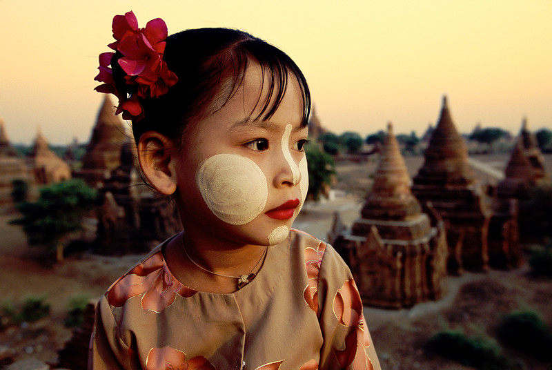 Burmese girl wearing thanaka face paint atop temple in Pagan, Burma