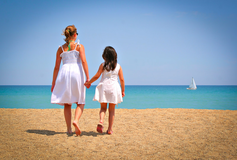 Two girls holding hands walking by the beach