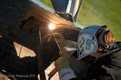 Young woman welding farm equipment
