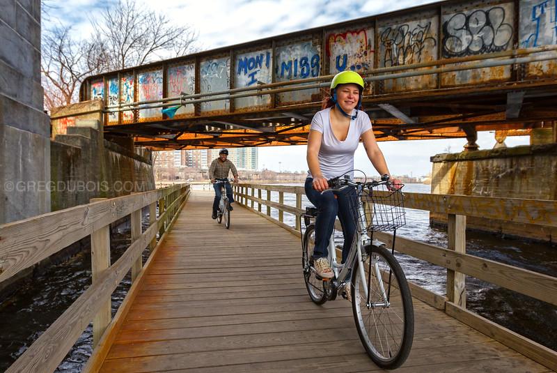 Zagster Bicyclists under BU Bridge Biking over Charles River, Boston Massachusetts