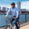Zagster Bicyclist with Back Bay Boston Skyline and Charles River Backdrop