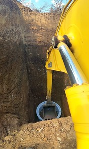 Large Construcion Pipe being placed in a large hole