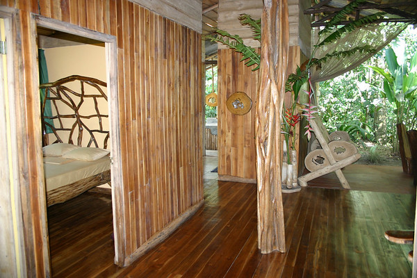 Danta Corcovado Lodge - bedroom, the edge of the living room, with the bathroom's lavatory and hanging mirror in the background