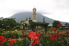 Beyond the florescence of the canna plants - and the church overlooking the Fortuna Town Square - with the cloud capped Volcan Arenal, a strato volcano along the distal horizon - Alajuela province (western)