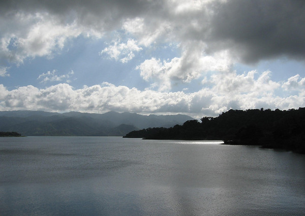Laguna Arenal (Lake Arenal) - a cumulus cloud shad across the largest landlocked body of water in Costa Rica, with a surface that covers nearly 33 sq. mi. (85 sq. km), and a depth of around 200 ft. (61 m) - with the Cordillera de Tilaran (mountains) along the distal horizon, at cloud level - Alajuela province