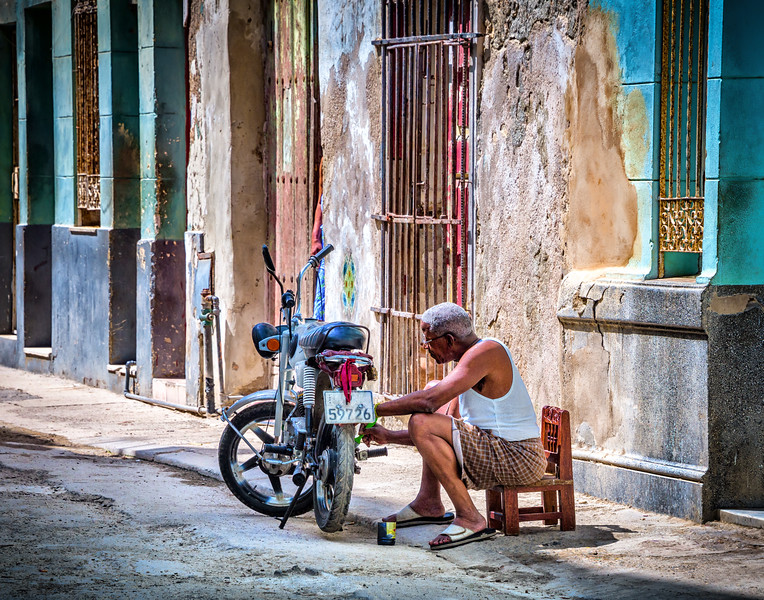 Old Havana, CUBA - March 19, 2016.  Man working on motor scooter in street of Old Havana, Cuba.