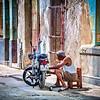 Old Havana, CUBA - March 19, 2016.  Man working on motor scooter in street of Old Havana, Cuba.