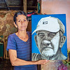 TRINIDAD, CUBA - March 22, 2016.  Beautiful Cuban woman holding a painting of her father in Trinidad, Cuba.