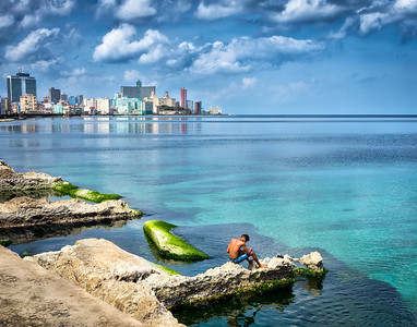 Old Havana, CUBA - March 19, 2016.  Boy sitting by the water on the Malecon on a sunny day in Old Havana, Cuba.