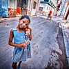 HAVANA, CUBA - March 27, 2016.  Cuban girl standing in street with her doll in Old Havana, Cuba