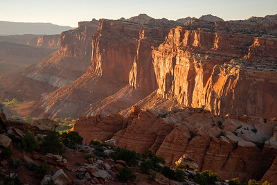 Sunset light shines on the red rock cliffs of the Fremont River Valley in Capitol Reef National Park in Utah.