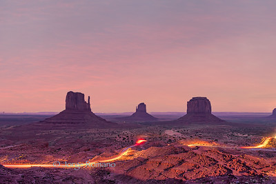 Long exposure of Monument Valley at night with cars illuminating the loop-tour dirt road
