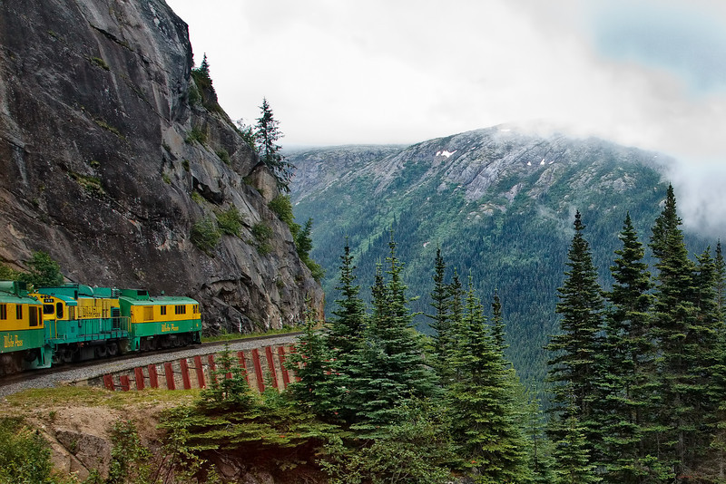 Train glides by Slippery Rock.  This portion of the route was completed in the harsh winter of 1898 - 1899.  Workers drilled blasting holes by hand while roped to sheer granite cliffs.<br /> White Pass & Yukon Route, Skagway, AK.<br /> July 13, 2010.