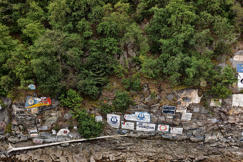 """Cliff wall along the harbor in Skagway that serves as the town's unofficial register of all the ships that """"put in.""""<br /> Skagway, AK.<br /> July 13, 2010."""
